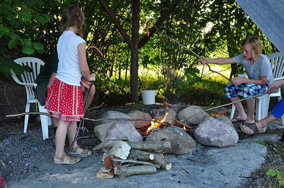 Barn grillar korv runt en eld